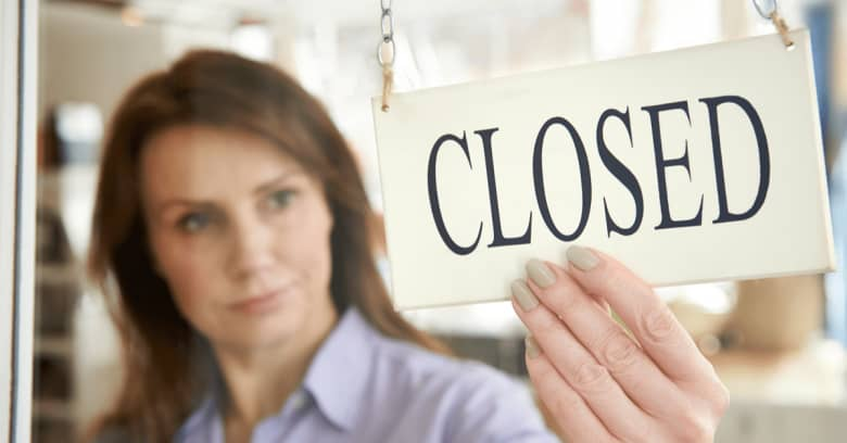 a woman puts a 'closed' sign up at her place of business