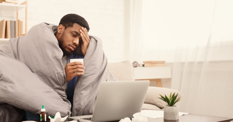 A man sits at home sick with a blanket wrapped around him and a computer in front of him