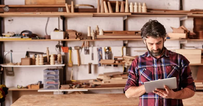 A small business owner stands in his woodworking shop looking down at a tablet while reading about the CARES Act