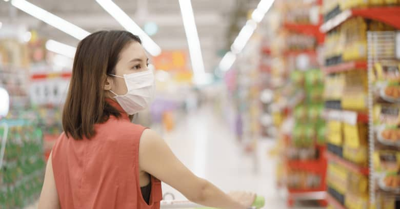 A woman is wearing a medical mask while she shops for groceries