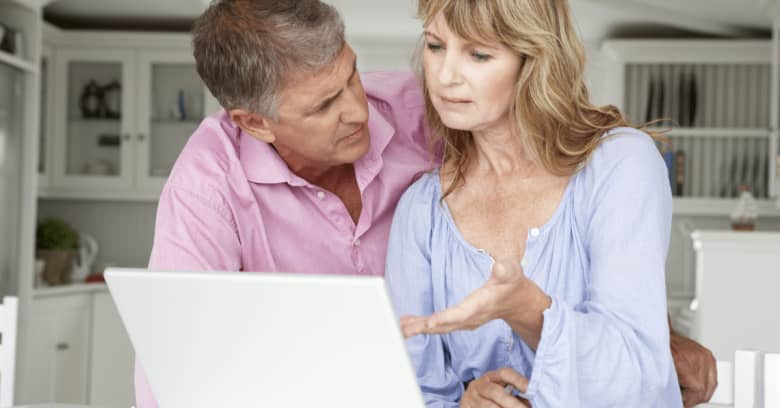 An older couple sits at a computer and discusses their finances in a serious manner