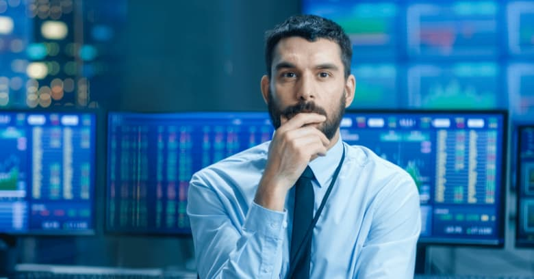 a stock trader is sitting at a desk in front of a computer in a stock exchange