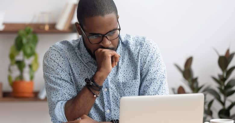 a man looks anxious while looking at a computer