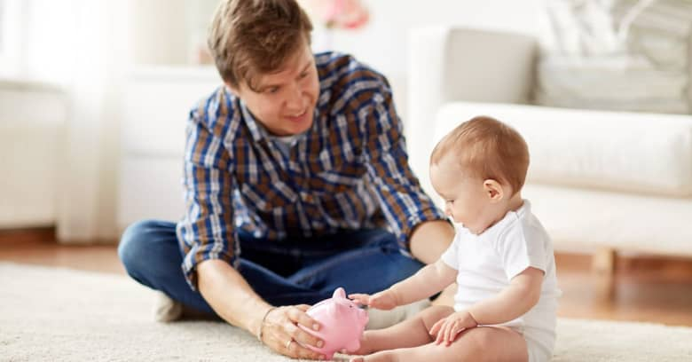 Toddler learning about money from parent