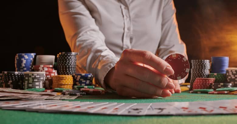 A dealer in a casino shuffles a deck of cards at a poker table