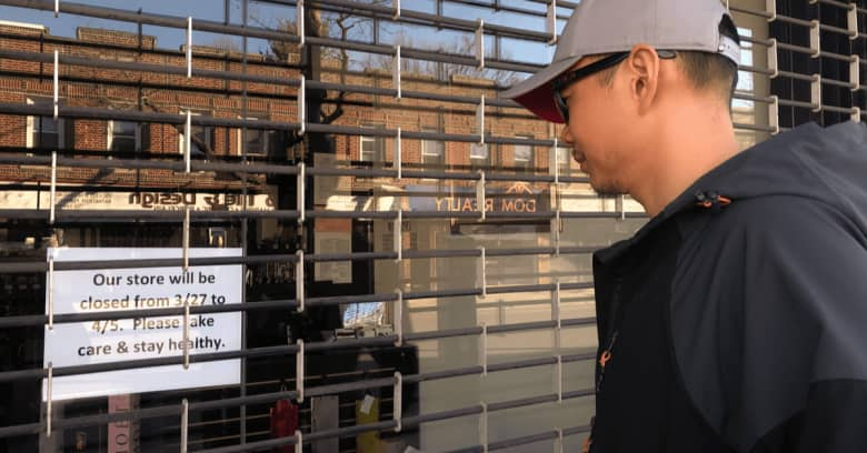 a man looks at a sign in the window of a business closed for the coronavirus