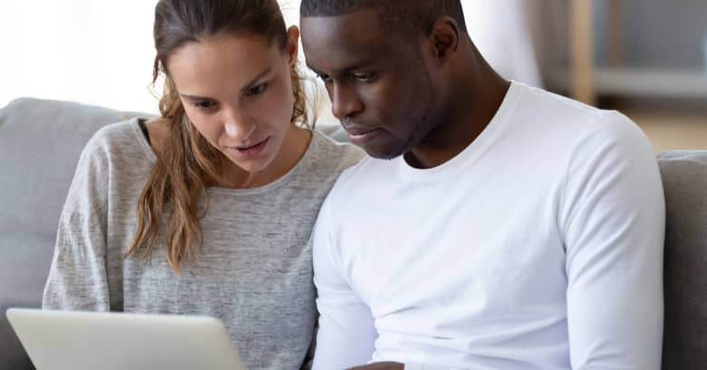 a couple looks at their computer to see if they are eligible for coronavirus relief support