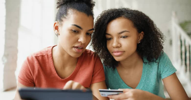 Two girls sit on a couch looking at a charity organization's website as they prepare to donate money