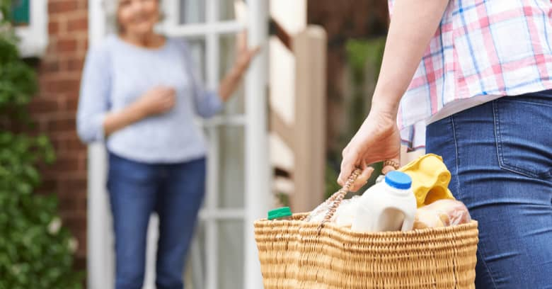 A person brings groceries to the home of an elderly neighbor