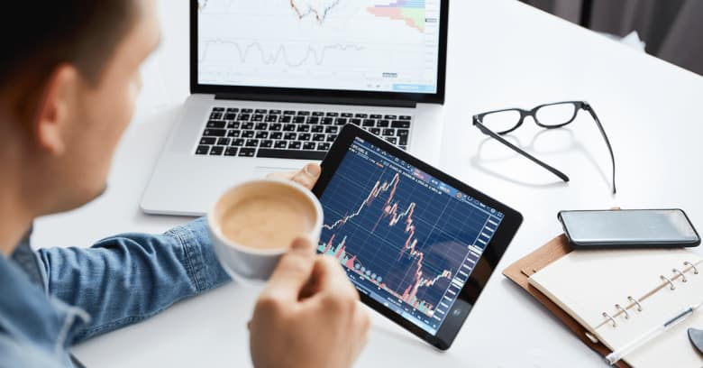 a man drinks a cup of coffee while looking at the stock market on his computer tablet