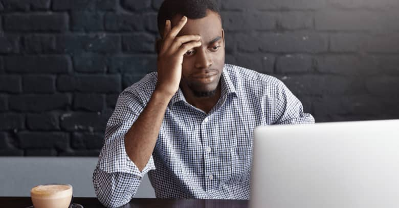 a man looks at his computer with worried facial expression and hand gestures