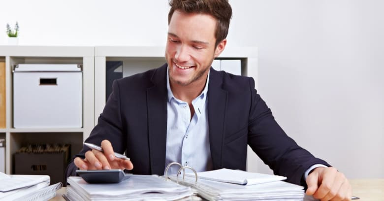 a man is smiling while pressing the buttons of his calculator and taking notes