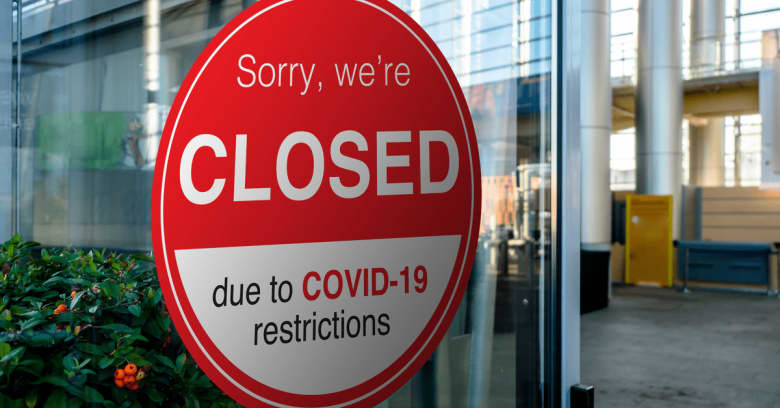 A round sign reads 'Sorry, we are closed due to COVID-19 restrictions.'