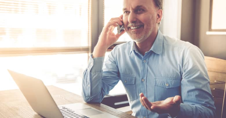 A man smiles while speaking on the phone with his mortgage company