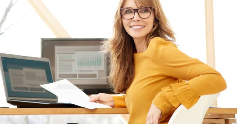 sitting woman with glasses holding a document