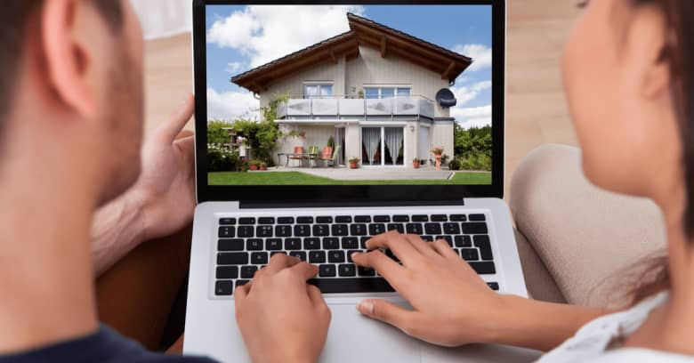 a couple looks at the laptop screen showing a house