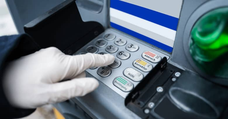 A gloved hand is seeing operating a bank ATM