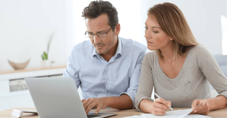 A couple works through their finances with a computer in front of them.