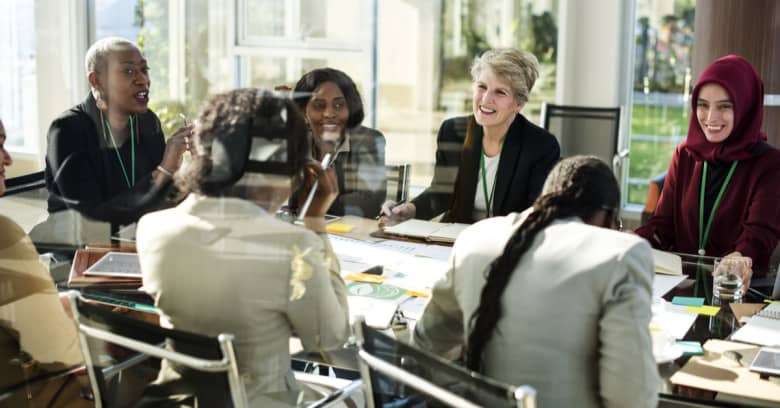 Several women sit in a glass meeting room discussing the financial institution they run