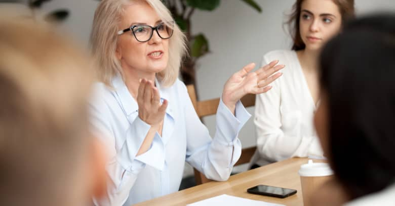 An older woman sits at a conference table with younger people to help them learn about personal finance