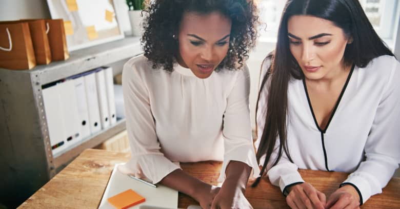 Two women are gathered in front of a computer learning about personal finance for women