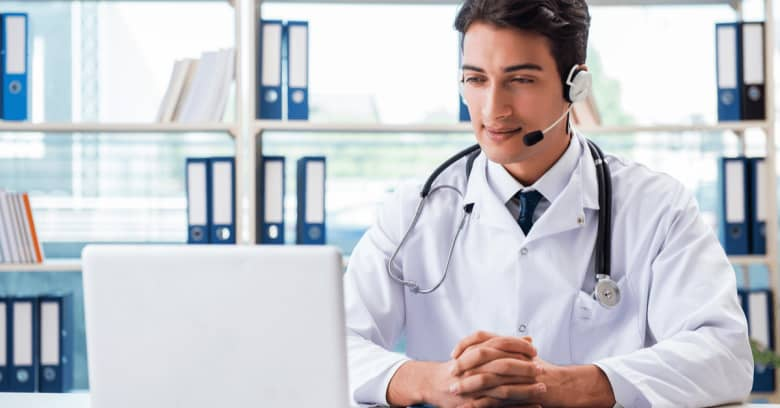 a doctor is seen at a desk conducting a telehealth appointment with his patient.