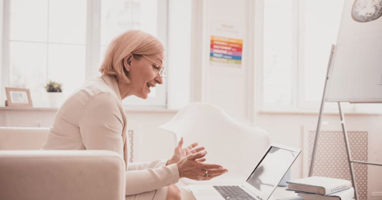 a therapist speaks with her client via online meeting.