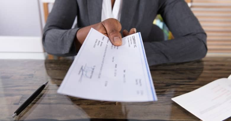 Woman handing over paycheck