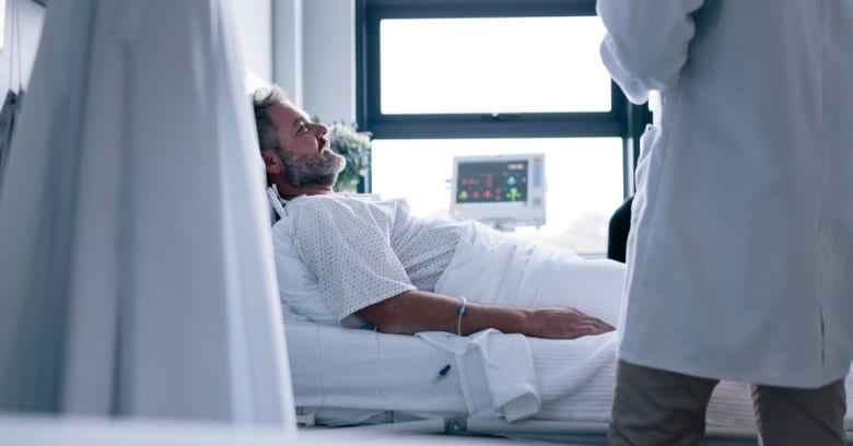 A man lies in a hospital bed recovering from coronavirus