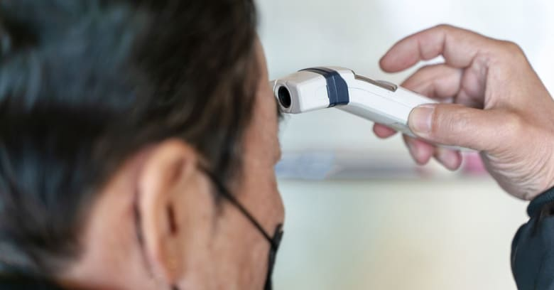 A man's temperature is checked as part of a screening process for coronavirus