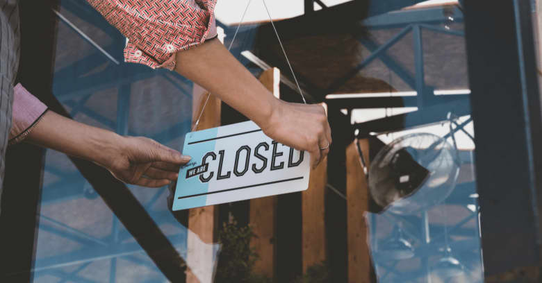 A business owner puts a 'closed' sign on the front door of her place of business