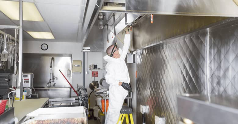 a commercial cleaning employee cleans an industrial kitchen while wearing full protective gear