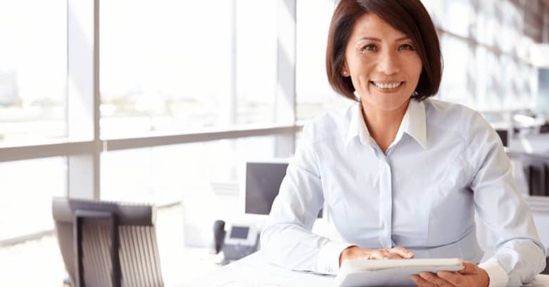 a woman sits at a desk looking at papers with a happy expression