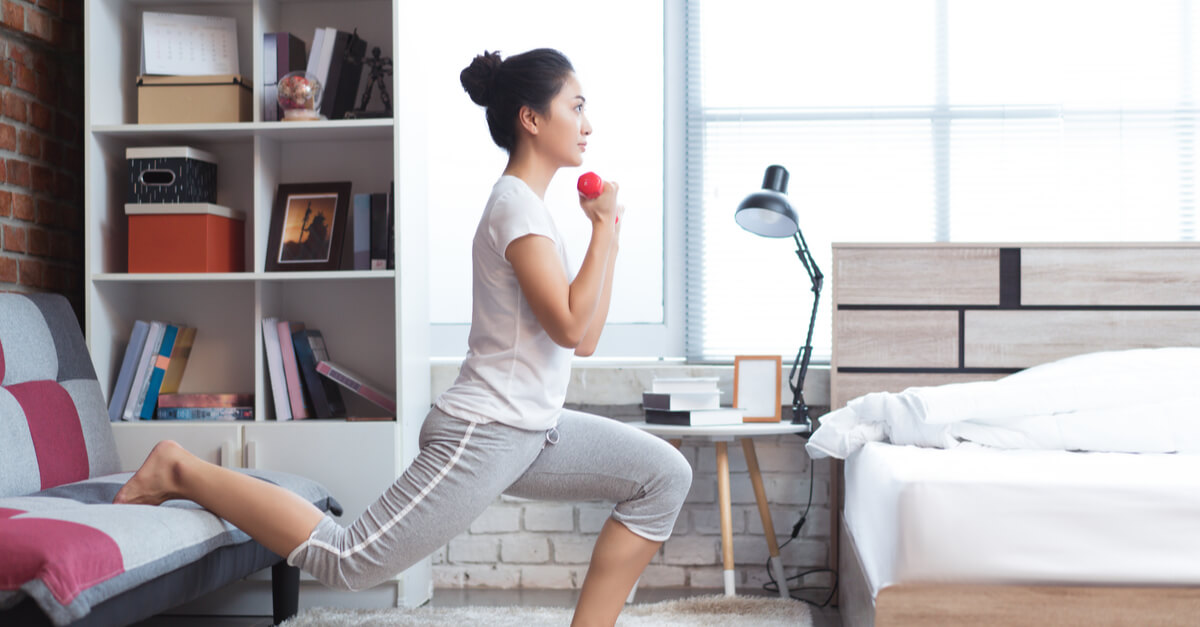 A woman works out in her bedroom before starting her workday as a remote employee.