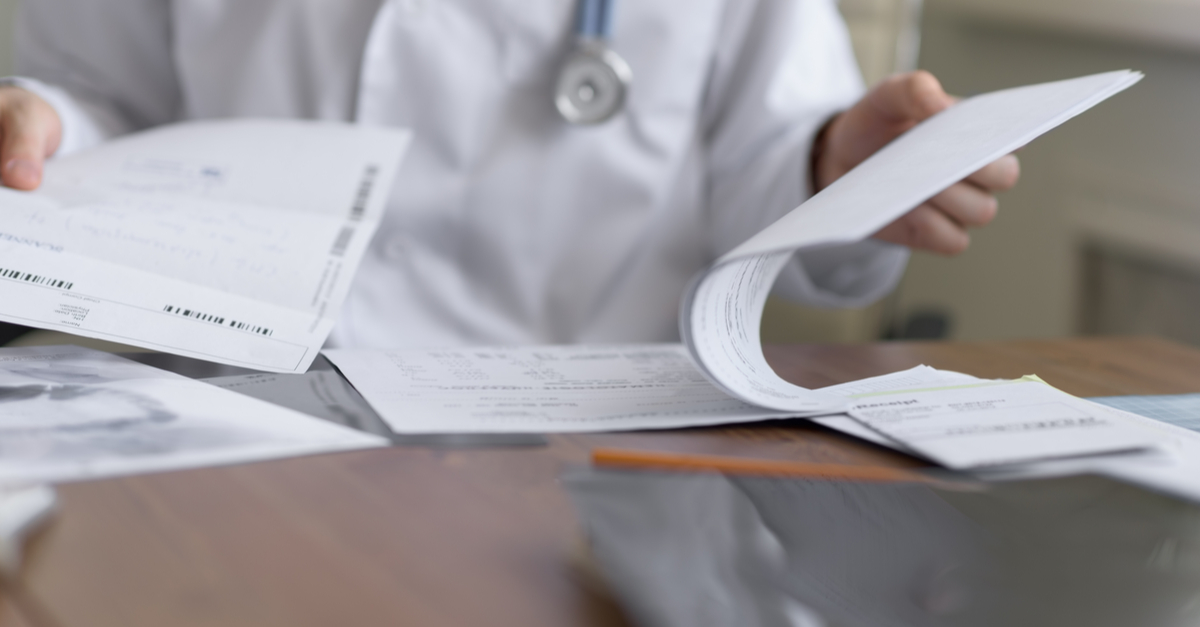 A doctor fills out medical paperwork in response to coronavirus.
