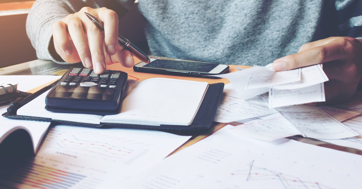 A man sits a desk working on a budget with a calculator and many papers.