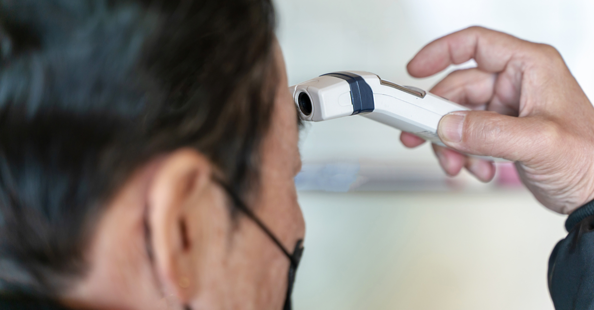A man's temperature is checked as part of a screening process for coronavirus.