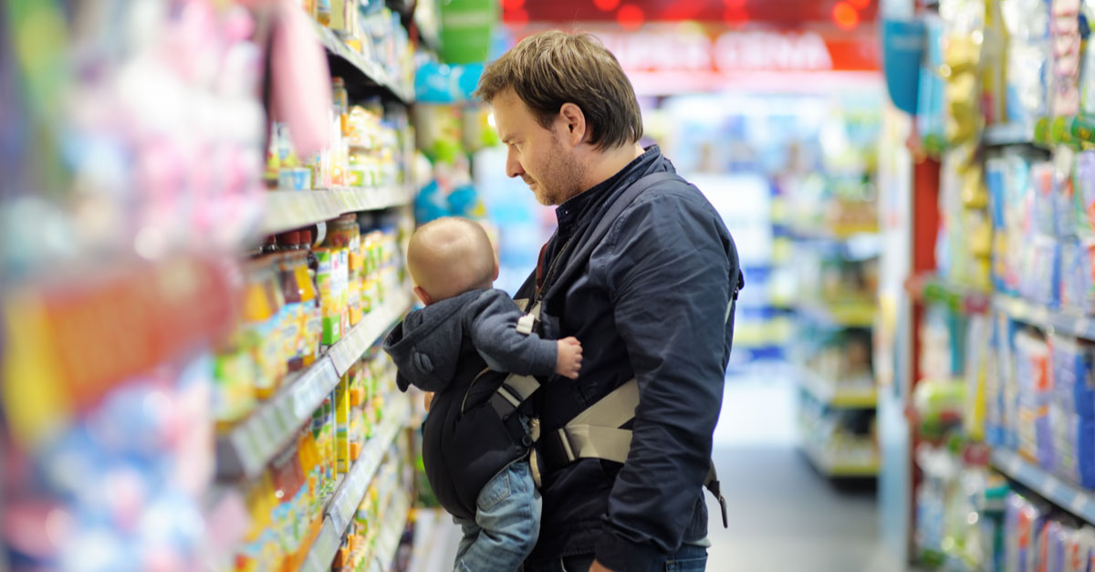 A father shops for generic baby items in the grocery store with his baby
