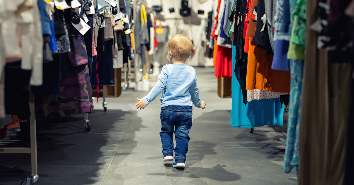 A baby walks between racks of clothes at a resale store