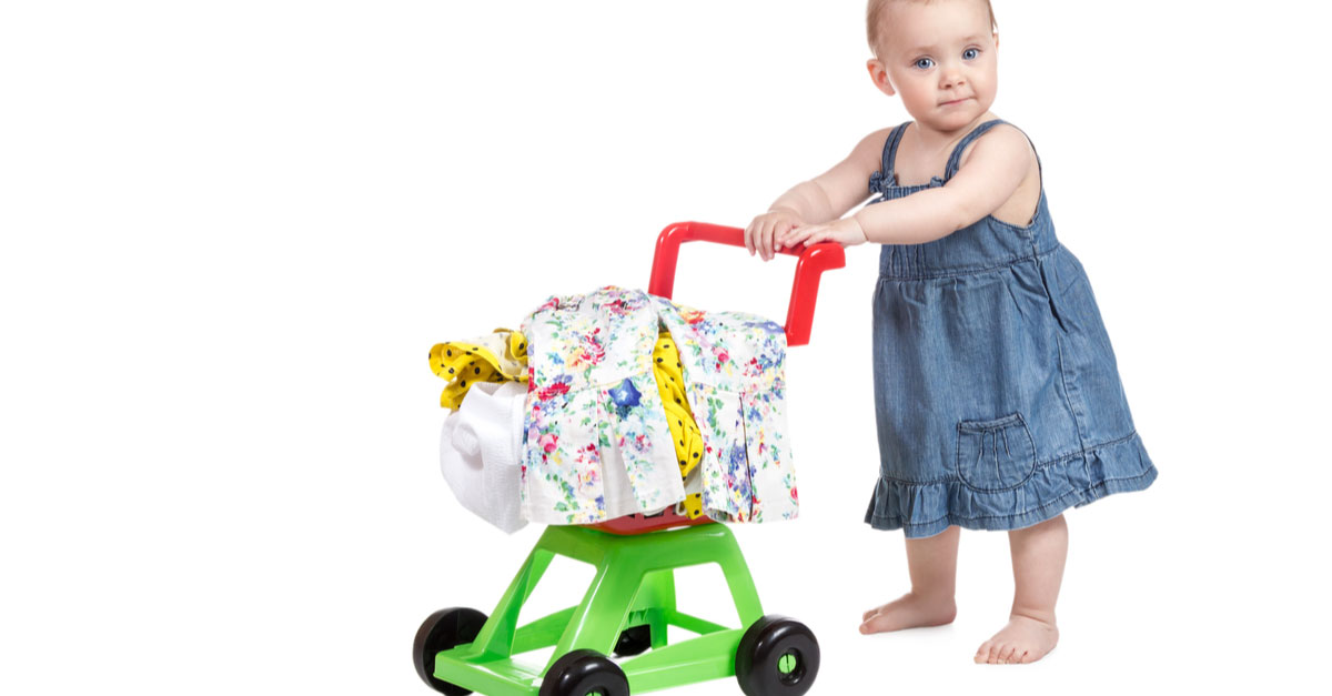 A baby walks with a toddler shopping cart with baby clothes in it