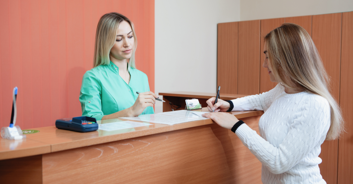 A woman is at the front desk of a medical office where she is checking in for her appointment with the receptionist