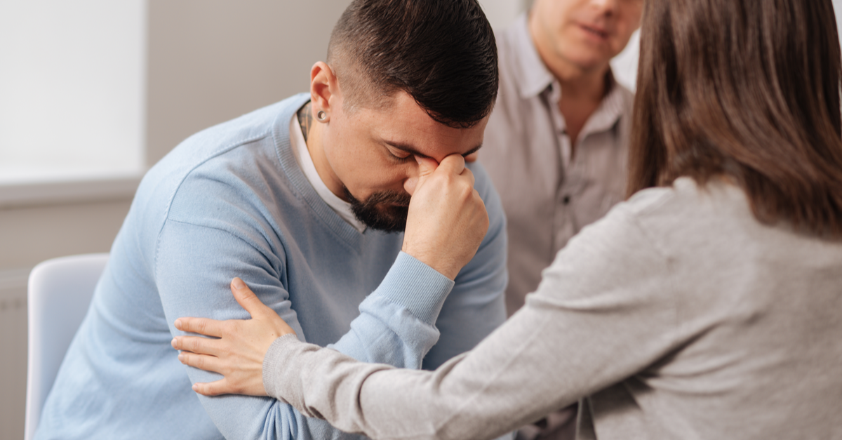 A man in distress in the therapist's office is being comforted by his female therapist while another man looks on.