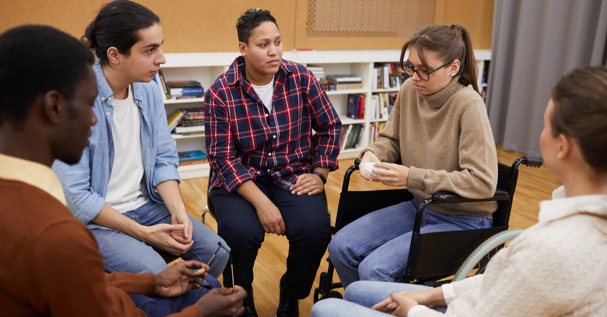 Several people in group therapy are listening with concerned looks on their faces while one member talks