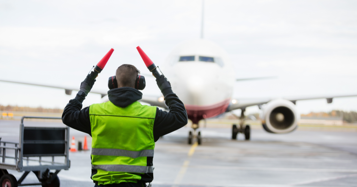 A member of a flight ground crew directs a commercial airplane into a terminal