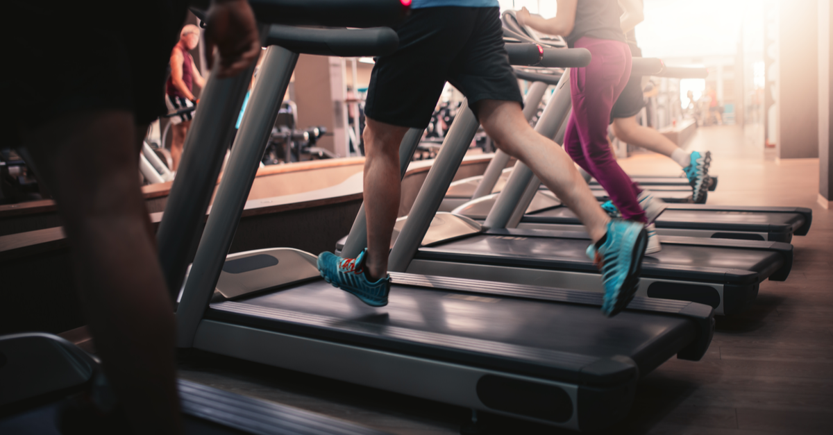 Patrons of a gym can be seen running on treadmills.