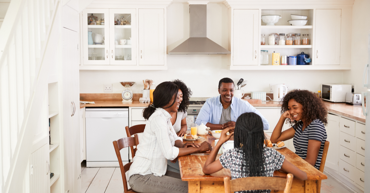 a family consisting of parents and teenage children has a meal together at a table in the kitchen