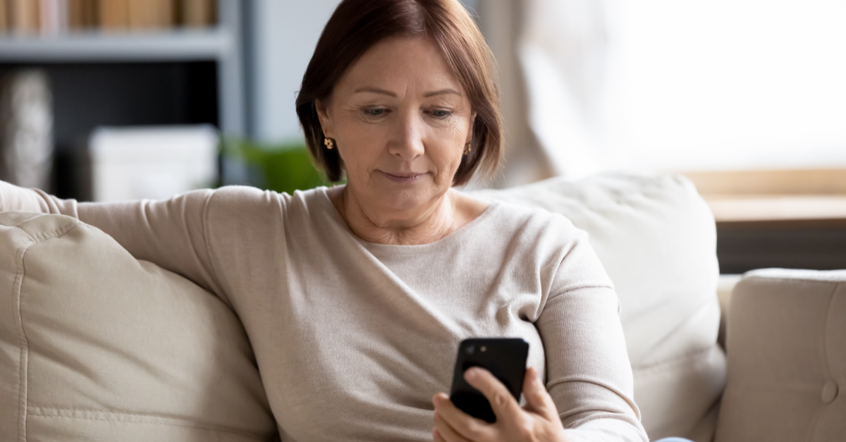 a woman looks at her phone and considers her retirement investments