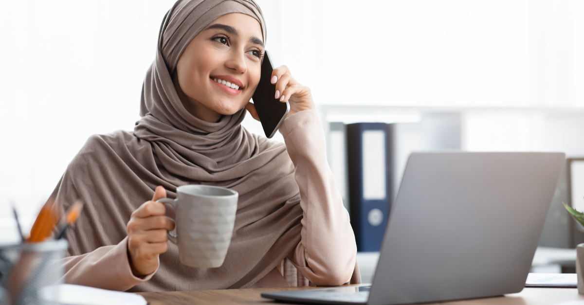 a small business owner is speaking on the phone while holding a cup of coffee