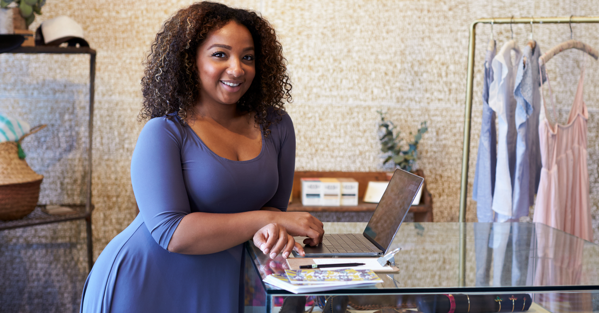 A small business owner, alone in her place of business, looks at the computer to learn about the CARES Act