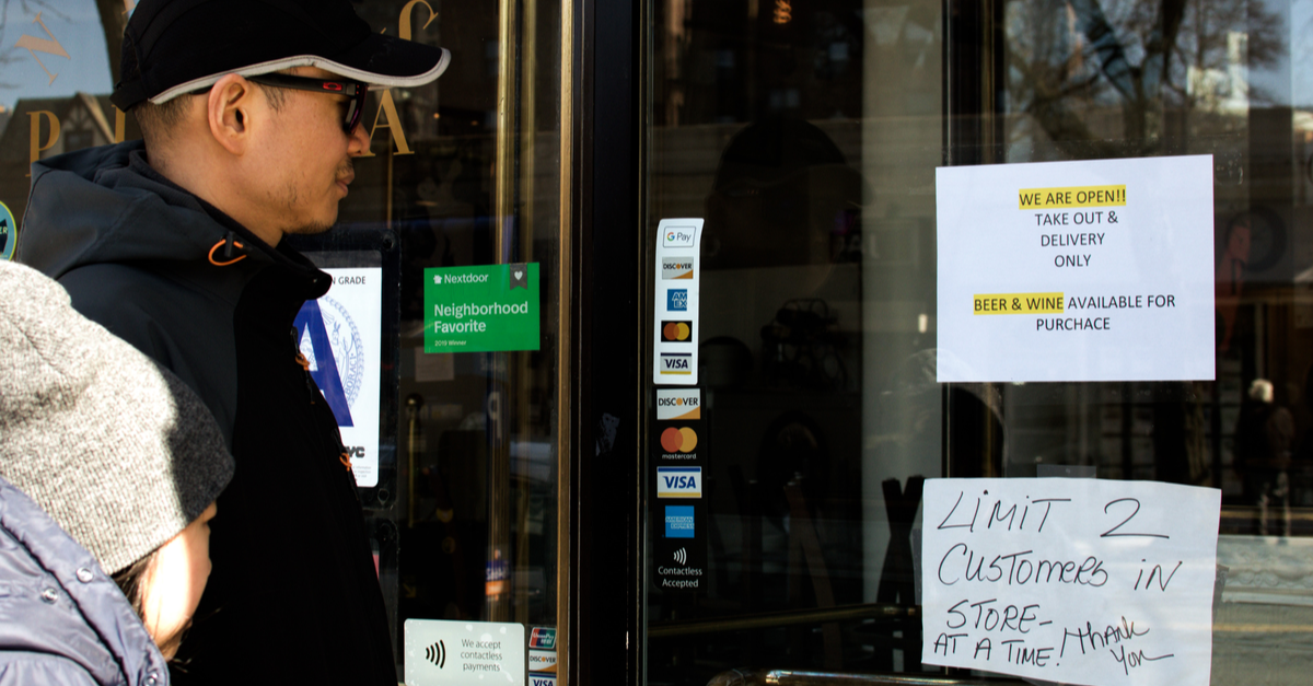 A couple stands outside a place of business that has reduced its business hours due to the coronavirus